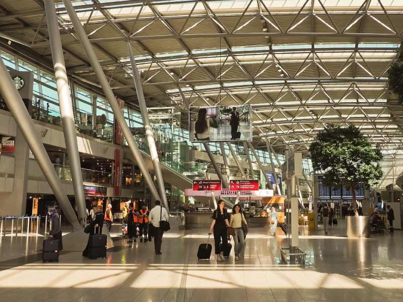 Personas llevando equipaje al counter del aeropuerto